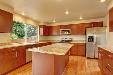 32672744 - kitchen with bright wooden cabinets, steel appliances and granite tops. kitchen room has kitchen island